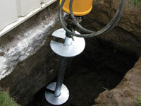 Installing a helical pier system in the earth around a foundation in Columbia