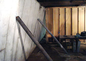 A severely tilting foundation wall propped up by steel beams in Franklin.