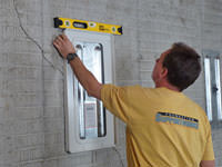 Positioning a wall plate cover on a foundation wall in Greer.