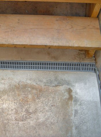 A grated basement drain weeping tile system for use with flooded hatchway doors